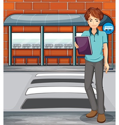 A man holding a book near the bus stop vector image