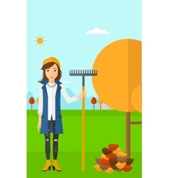 Woman with rake standing near tree and heap of vector