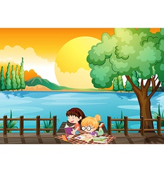 Two girls studying at the wooden bridge vector image
