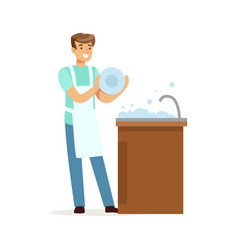 young smiling man washing dishes in the kitchen vector image