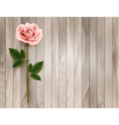 Single pink rose on an old wooden background vector
