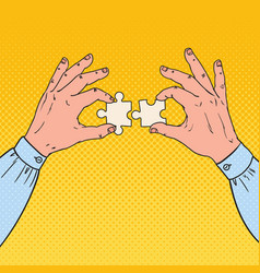 pop art male hands holding two puzzle pieces vector image