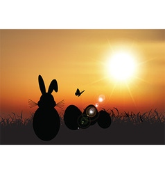 Easter bunny sat in grass against a sunset sky vector image