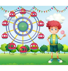 A boy holding a lollipop beside a ferris wheel vector image
