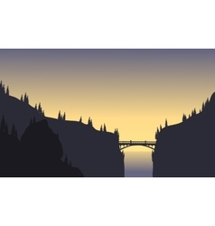 Silhouette of bridge connecting two cliffs vector