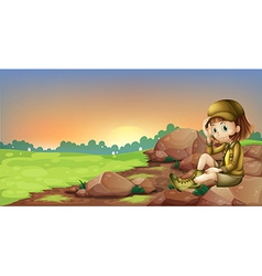 A female explorer relaxing above a rock vector