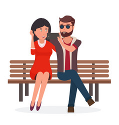 Young couple sitting on a bench doing selfie vector