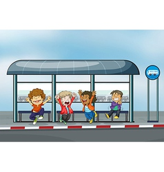 Four happy kids at the waiting shed vector image