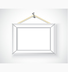 White picture frame hanging on the wall vector