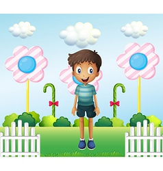 A boy in the garden with flower lollipops vector