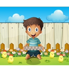 A boy with an empty egg tray and the little chicks vector image vector image