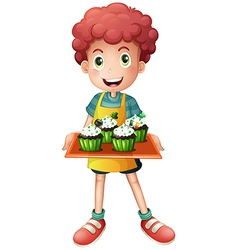 A boy holding a tray of cupcakes vector image vector image