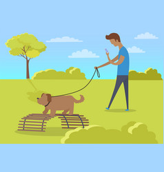 Young boy walking with dog and using phone in park vector