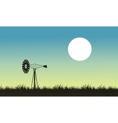 Silhouette of windmill and grass landscape vector