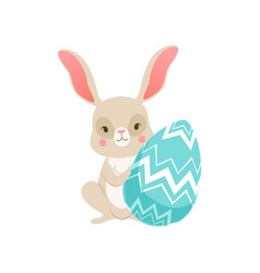cute cartoon bunny sitting holding blue egg funny vector image vector image
