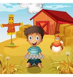 A boy holding an empty egg tray at the farm with a vector image vector image