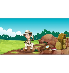 A boy wearing a hat sitting on a rock vector
