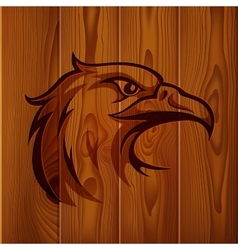 Eagle head vintage logo on realistic brown wood vector image