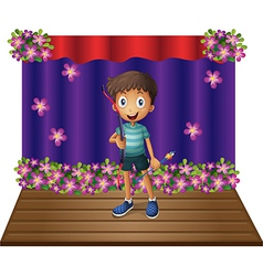 A stage with a young boy holding a bow and arrow vector image vector image