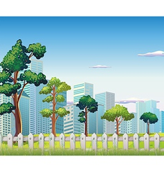 Trees inside the fence near the tall buildings vector