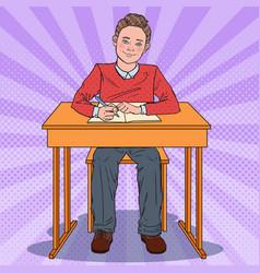 Pop art happy schoolboy sitting at school desk vector
