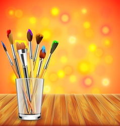 Art brushes in glass on wooden table colorful vector image vector image