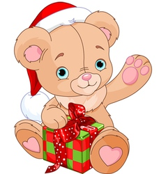 Christmas teddy bear holding gift vector