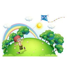 A boy playing with his kite at the hilltop vector image