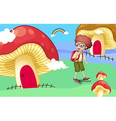A boy near the giant mushroom houses vector image