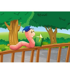 A worm reading a book above the wooden fence vector