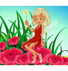 A fairy holding a wand sitting at the red flowers vector
