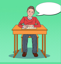 Pop art happy schoolboy sitting at school desk vector