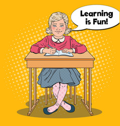 pop art happy schoolgirl sitting at school desk vector image vector image