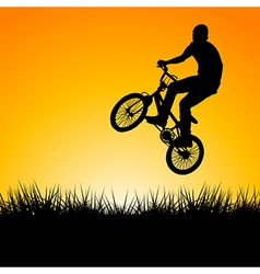 Silhouette of a biker jumping in the sunset vector