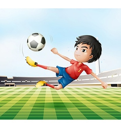 A boy playing soccer in the soccer field vector