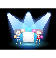 Two young cheerdancers at the stage with an empty vector