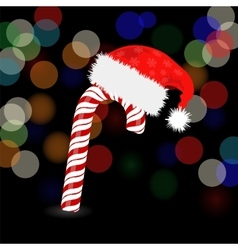 Candy cane and hat of santa claus vector