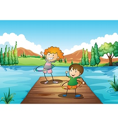 Two kids playing hulahoop at the river vector image