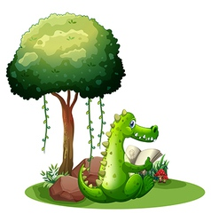 A crocodile reading beside the tree vector image