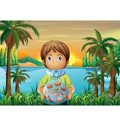 A boy standing near the riverbank while holding a vector image vector image