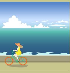 A girl on a bicycle rides along the sea shore vector