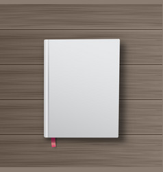 Realistic book with white cover on a wooden table vector