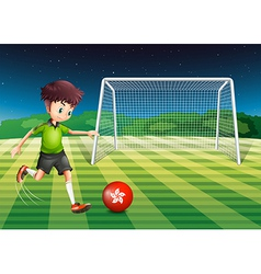 A young man kicking the ball with the flag of vector