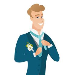 Young caucasian cheerful groom adjusting tie vector