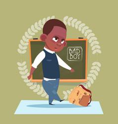 Small bad school boy standing over class board vector