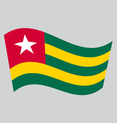 Flag of togo waving on gray background vector