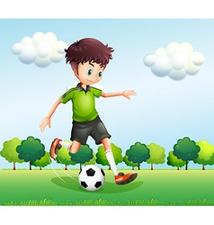 A boy with a green t-shirt playing football vector