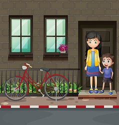Boy and mother in front of a house vector image vector image