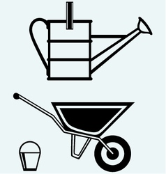 Garden wheelbarrow and watering can vector