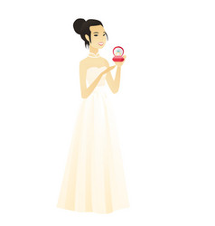 Young bride holding a wedding ring in a box vector